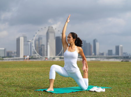 outdoor image of an asian chinese woman practising yoga with the landscape