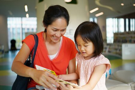 Asian Chinese Mother and Daughter visiting the library and browsing through books Stock Photo