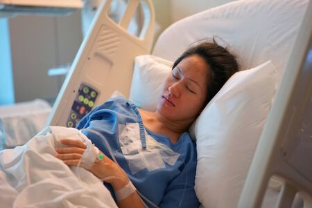 Asian Chinese Woman patient lying in the hospital bed asleep