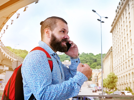 The bearded man got a good news by phone. The man with mobile phone is speaking on the street.