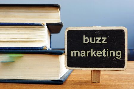 Text sign showing buzz marketing. The text is written on a small wooden blackboard. The book, pen, wooden background are on the photo.