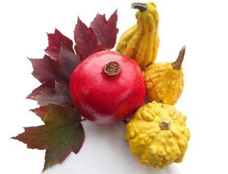 Red pomegranate encircled with yellow gourds and fall leaves, isolated on a white background Stock Photo