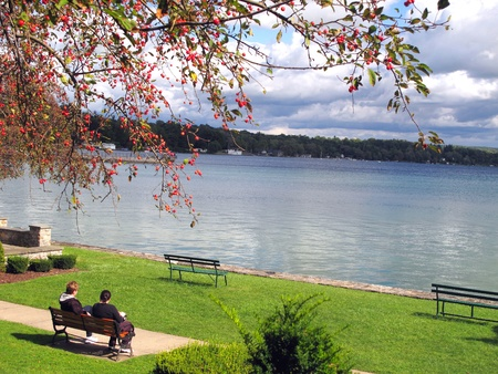 Two people sitting on a park bench with a view of the lake. Framed in the foreground with a colorful tree