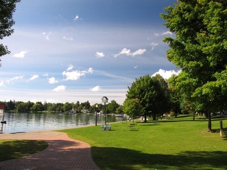 Bright Sunny Park with Trees and Lake in the Distance