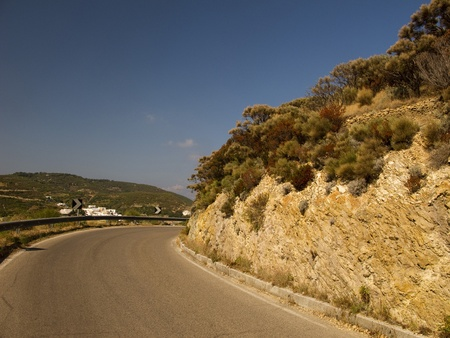 Winding road curving around a mountain pass photo