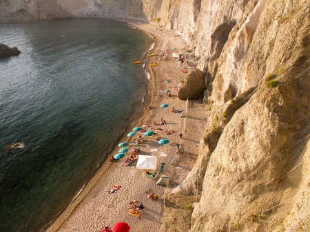 Aerial view of swimmers and beach umbrellas at beach with cliff Stock Photo