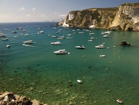 Boats anchored along a green blue sea