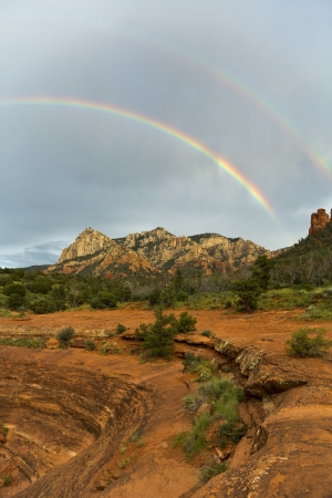 arching: Double rainbow arching over mountains of Sedona at sunset Stock Photo
