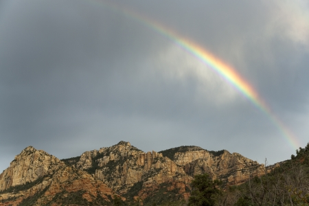 Rainbow arching over mountains of Sedona at sunset Stock Photo
