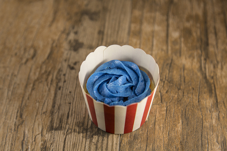 Cupcake with blue frosting in Fourth of July cup. Shallow depth of field.