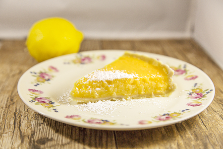 Wedge of Lemon Tart isolated on a wooden table Stock Photo
