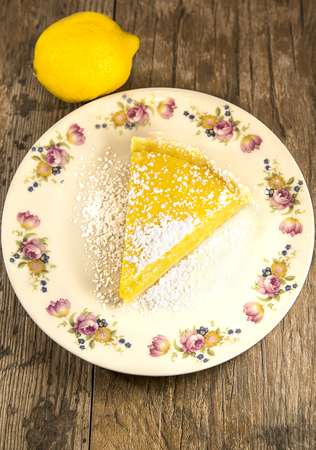 Lemon Tart slice on old fashioned plate, isolated on a wooden table