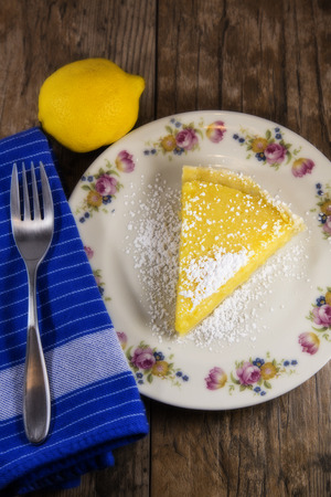 Wedge of Lemon Tart isolated on a woodtable, white plate with floral design. Lemon and blue napkin with a fork surrounding the plate.