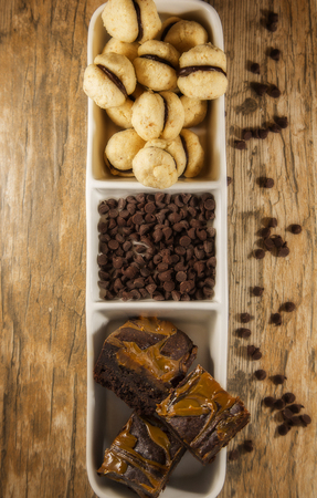 Display of bite size brownies, and round mini chocolate cookies displayed in a white serving dish, with chocolate chips