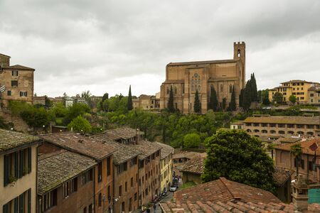 Panoramic view of Siena.  Homes, rooftops, church and cypress trees in full view.  Tuscany region of Italy.