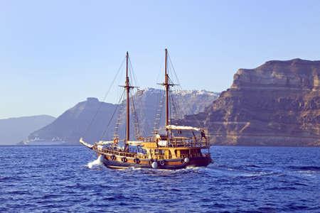 Wooden sailing boat sailing towards the island of Santorini photo