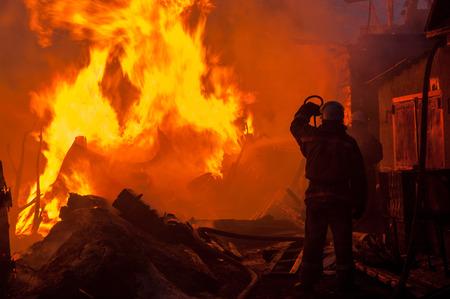 消防士の家および建物を消す 写真素材