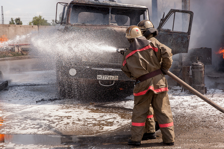Firefighters extinguish a car