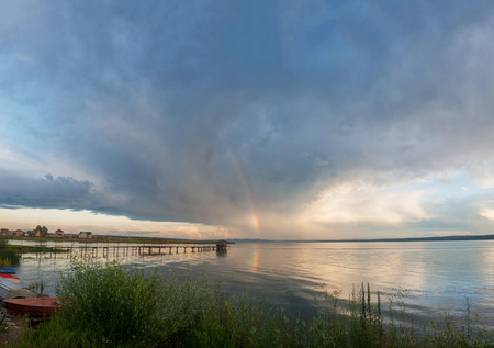 Colorful rainbow over lake and storm cloud with rain on background