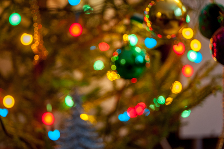 Pine branch with Christmas balls and fire in blur background