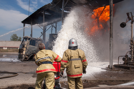Firefighters extinguish a car fire Stock Photo