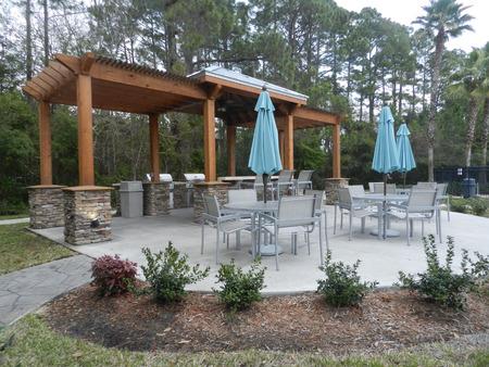 patio furniture: Patio furniture with umbrellas on stone patio near upscale condo building  - barbecue area style in Florida