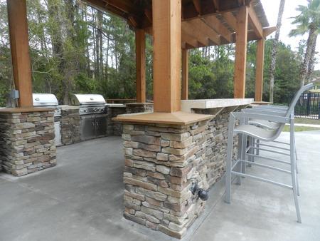 furniture: Patio furniture with umbrellas on stone patio near upscale condo building  - barbecue area style in Florida