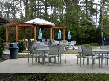 Patio Furniture With Umbrellas On Stone Patio Near Upscale Condo Building    Barbecue Area Style In