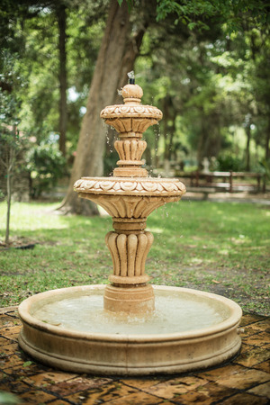 garden fountain: Old classic garden fountain with flowing water and blurred framed trees view on background