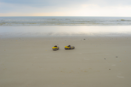 swim shoes: shoes of a man at sunset at the beach with the horizon in the background. refugee migrant