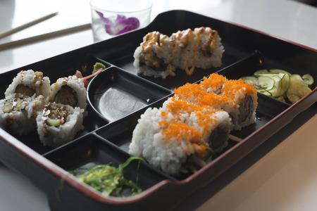 Sushi rolls Bento set served on black plate on white background