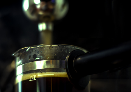 Coffee machine. Close-up of espresso pouring on black background 免版税图像