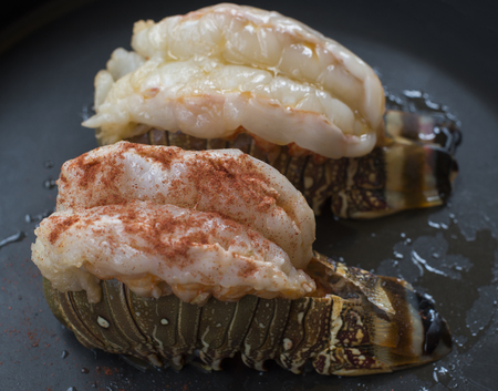 Pair of raw lobster tails in the oven food on a black background