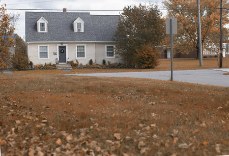 A view of a brick house with colorful autumn leaves on a bright fall day