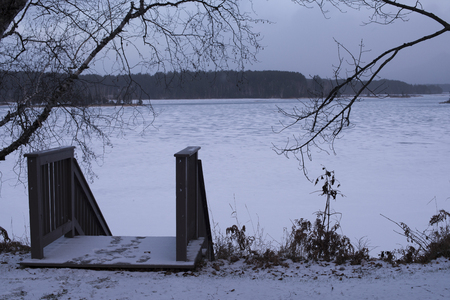 Picture of a white frozen lake in winter during snowfall, with fog, trees and wooden bridge 免版税图像