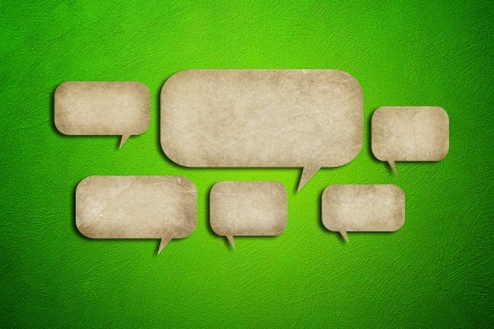 grunge paper speech bubbles on green cement background