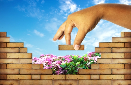hand building a brick wall ;build a house concept photo