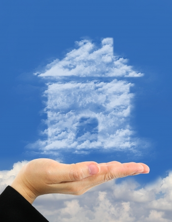man made structure: home symbol made of clouds  over hand Stock Photo