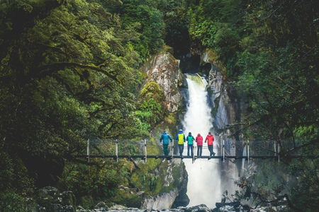 A group of hikers enjoying the view of Giants Gate Falls along the Milford Track