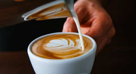 Latte art. Barista pouring milk into coffee cup Banque d'images - 128588692