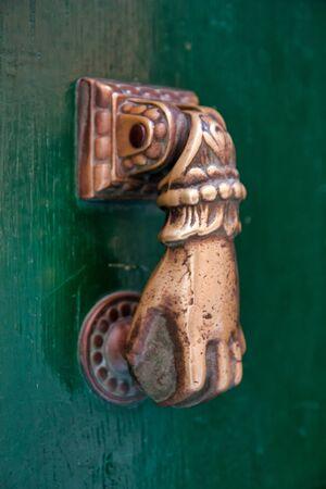 Door with brass knocker in the shape of a hand. Stock fotó