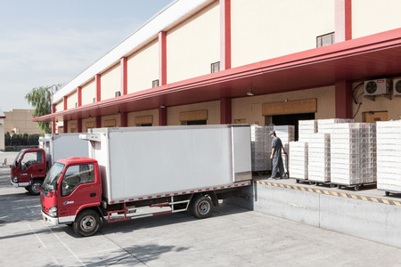 Food production factory and delivery trucks Editorial