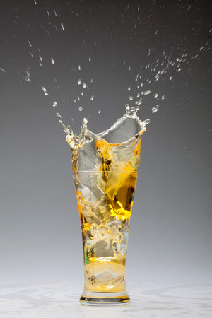 golden beer splashing from a glass