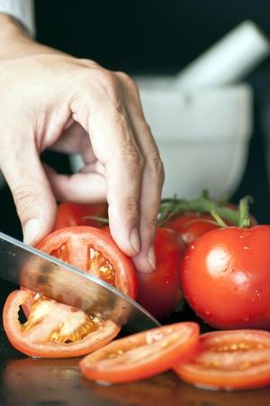 Chef Slicing A Tomato Stock Photo