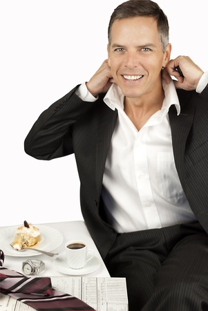 Smiling Businessman Loosens Collar Over Cupcake And Espresso photo