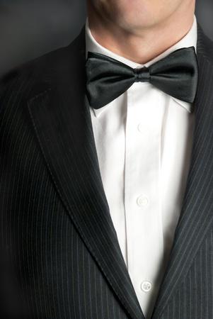 attire: A close-up shot of a man wearing a tux.