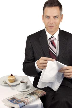 Confident Businessman Uses Napkin Over Espresso and Cupcake  photo