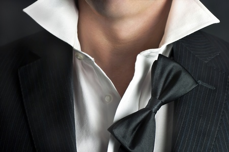 tie necktie: A close-up shot of a man in a tux with his bowtie hanging and his collar undone.