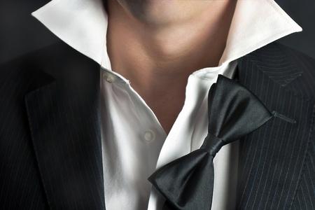 corbata negra: Un tiro de primer plano de un hombre en un tux con su suspensi�n de pajarita y su cuello deshecho. Foto de archivo