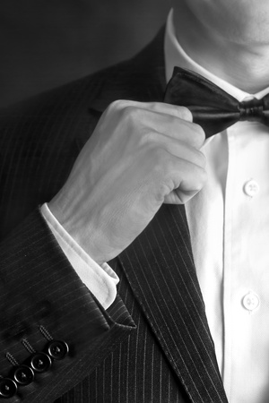 A B&W close-up shot of a man wearing a tux straightening his bowtie.